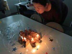 誕生日ケーキのろうそくを吹き消すスタッフ江本